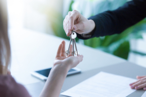 Woman getting keys to new rented own apartment, close up